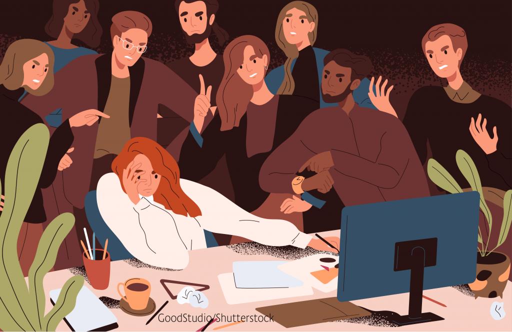 Frau sitzt umringt von Menschen am Computer und sieht verzweifelt aus.